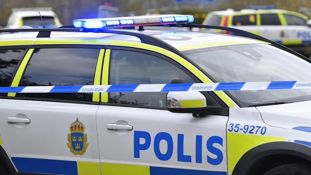 Polisbil framför avspärrningsband.