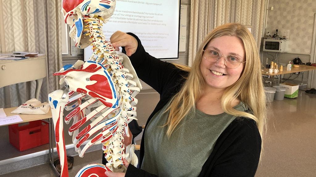 Annelie Salminen håller i en modell av ett skelett.