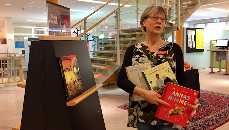 Annika Elmhag, barnbibliotekarie, står med massa böcker i famnen.