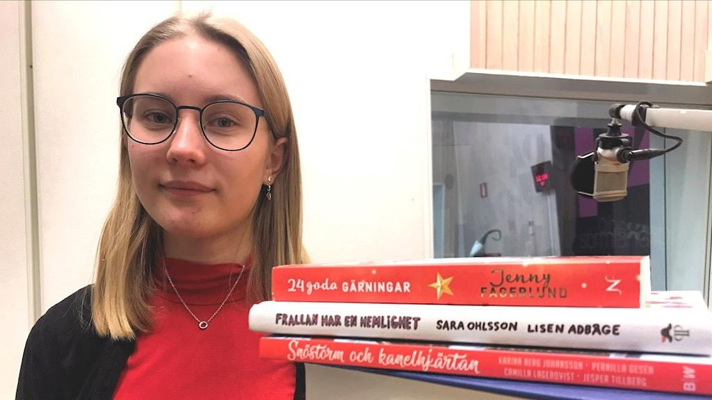 Agnes Lindholm står bredvid en trave böcker.