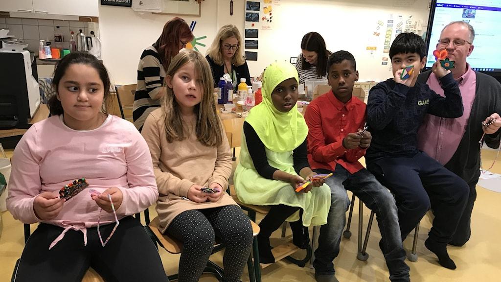 Läraren Bengt Hassler tillsammans med elever på grundsärskolan i Flen som visar upp pärlplattor.