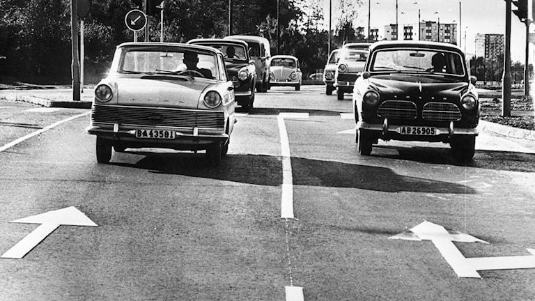 verige går över från vänster- till högertrafik. Bilden är tagen i Stockholm i det ögonblick som trafikanterna försiktigt fick byta sida, klockan fem på morgonen, den 3 september 1967. Ommålningen av gatumarkeringar fick ibland göras i efterhand; därför verkar bilarna köra mot enkelriktat.