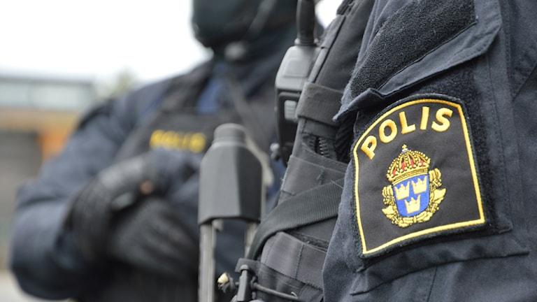Poliser med insatsmundering och automatvapen.