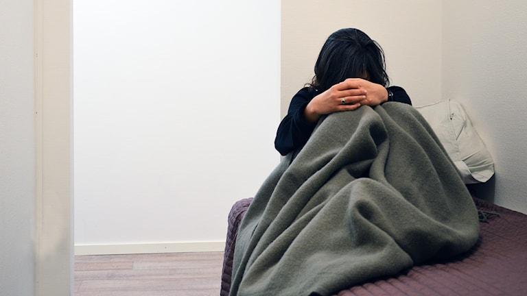 Kvinna med nedböjt huvud under filt