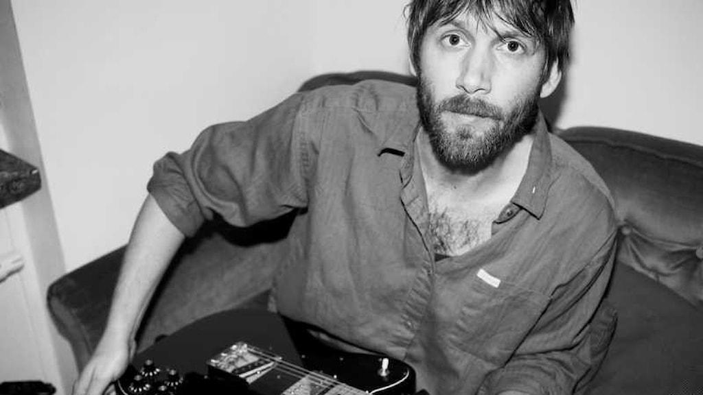 Musikern Adam Heldring. Svartvit bild. Adam sitter ner med akustisk gitarr i famnen.