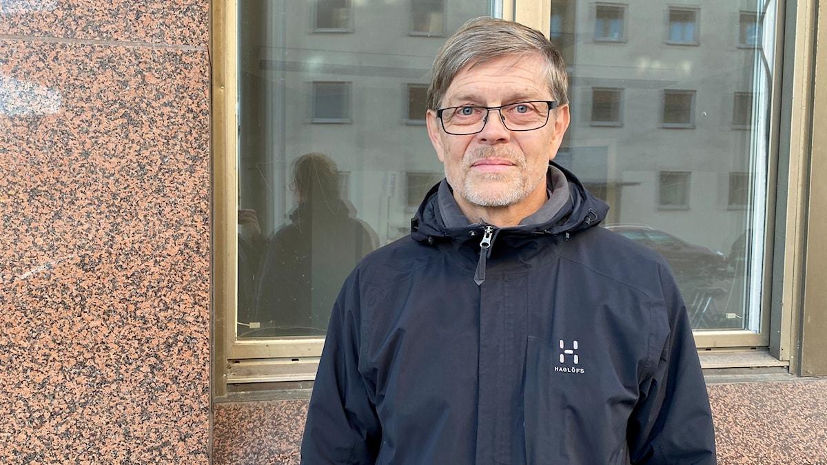 Signar Mäkitalo, smittskyddsläkare i Sörmland, står utomhus i blå jacka framför ett fönster.