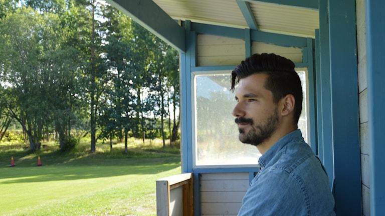 Man sitter i en kur och blickar ut mot en grön fotbollsplan. Foto. Annizeth Åberg/Sveriges Radio.