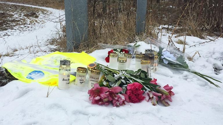 Ljuslyktor och blommor vid en Missing People-väst.