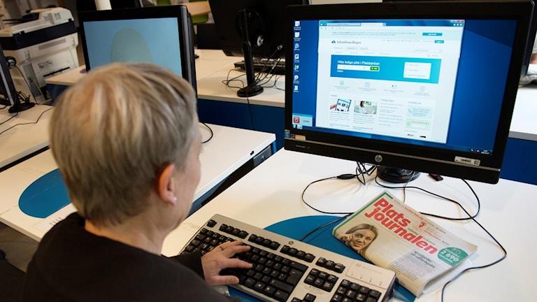 En person framför datorn.