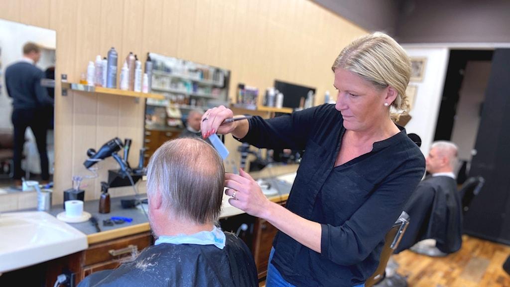 Frisören Johanna Nordvall i Nyköping klipper Lars-Göran Berg som har hår nedanför öronen.