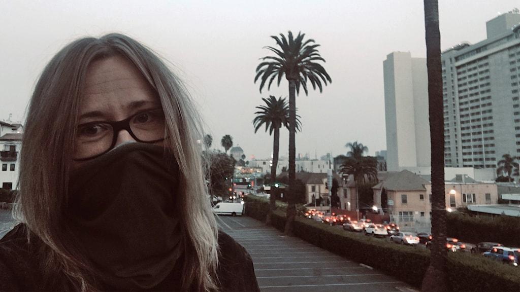 Sandra North, med halsduk framför munnen i stadsmiljö med dålig luft på grund av brandrök.
