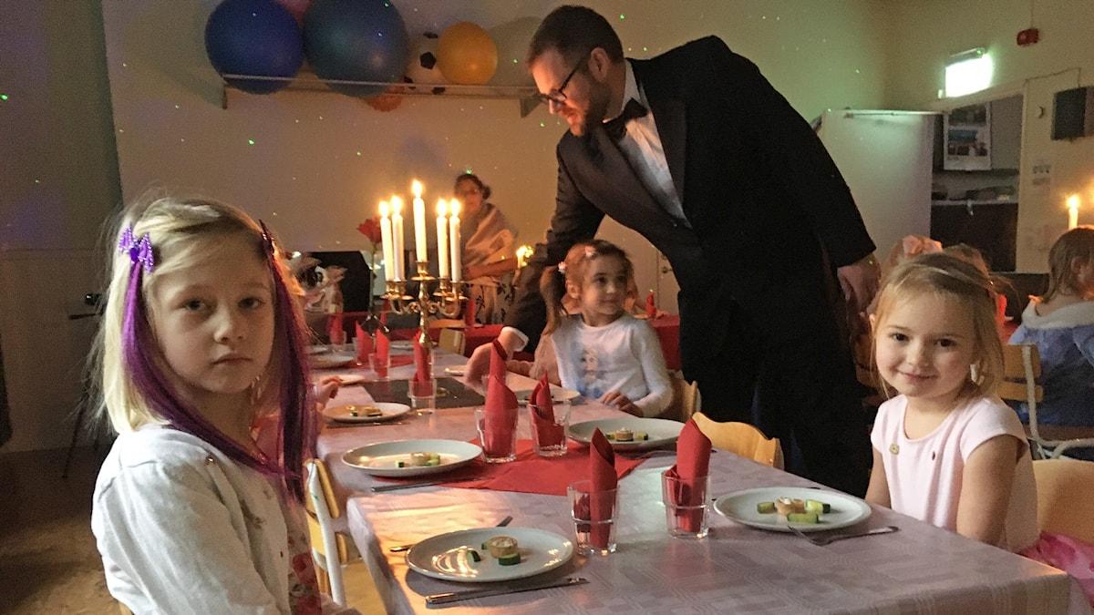 Tre flickor sitter vid ett uppdukat bord med tända ljus. Två av dem tittar in i kameran. En vuxen i smoking serverar.