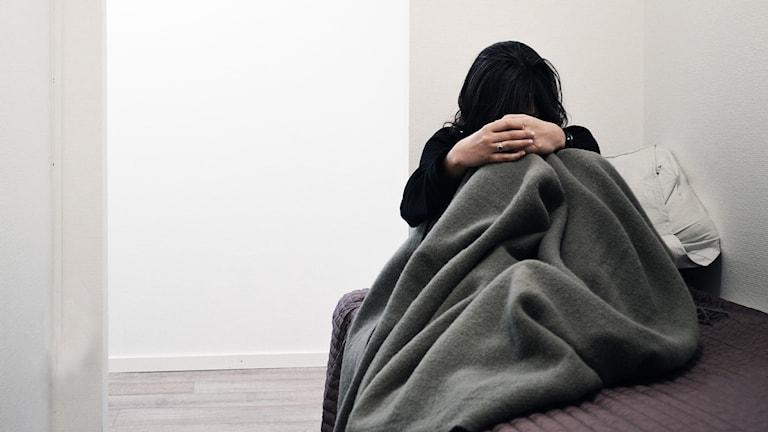 Ung kvinna sitter på säng, med filt om sig. Håret för ögonen.