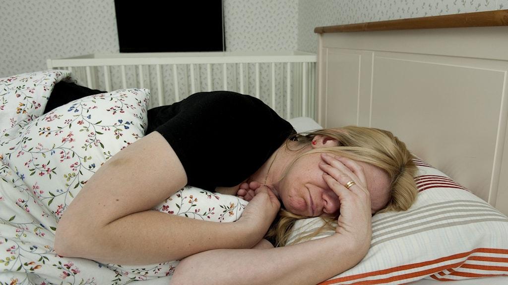 kvinna ligger i säng och håller för ögon med ena handen