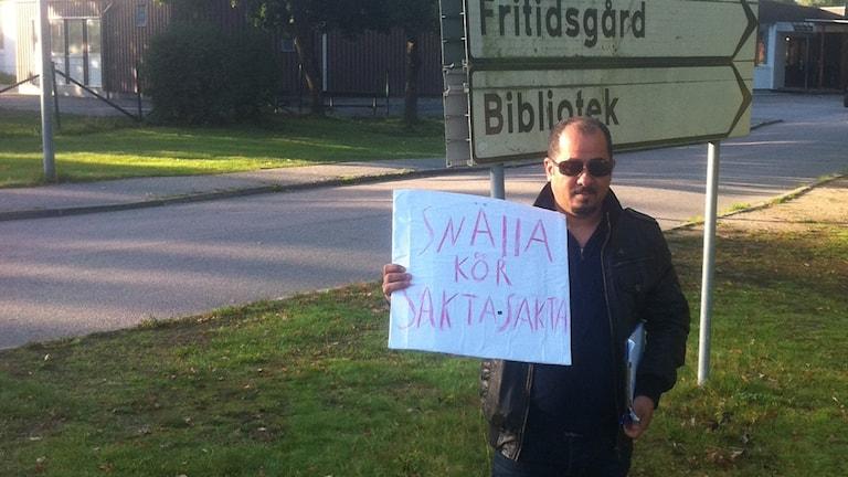 Man står med skylt utanför skola. Foto: Privat.