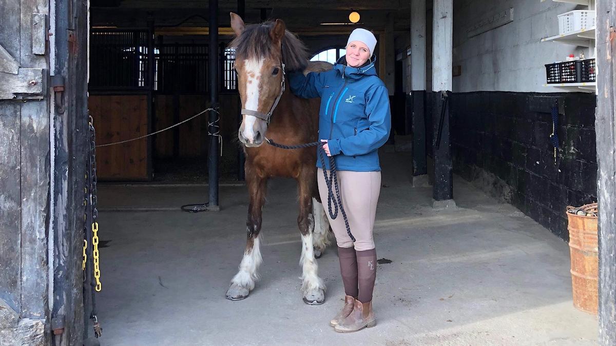 Emma Johansson tillsammans med en häst i ett stall.