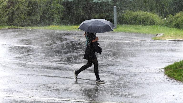 Kvinna springer i regn