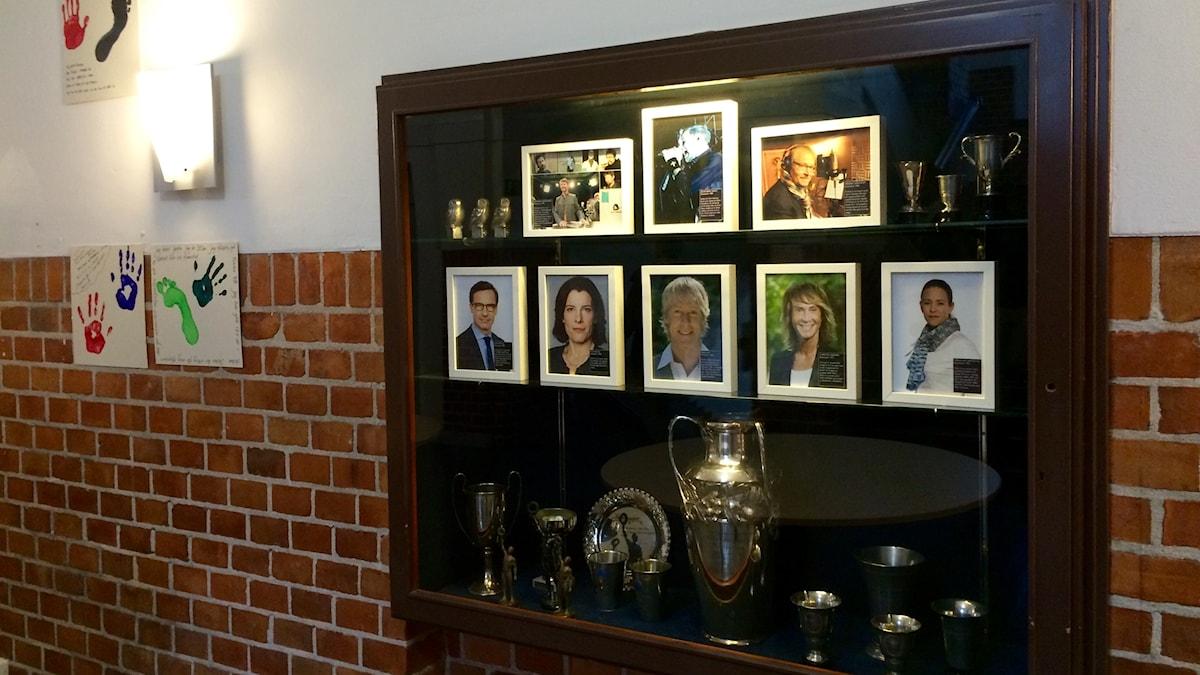 Många foton i ett glasskåp med ett porträtt av Jocke Berg högst upp i mitten.