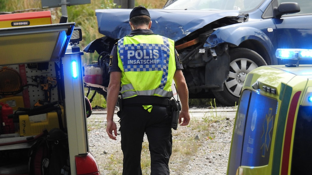 Polis som kollar på en förstörd bil.