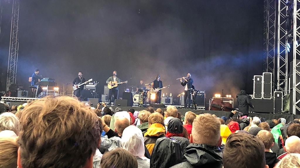 Publik ser på musiker som spelar på stor scen.