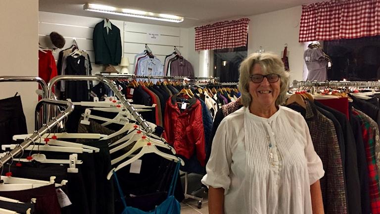En kvinna bland klädställningar.