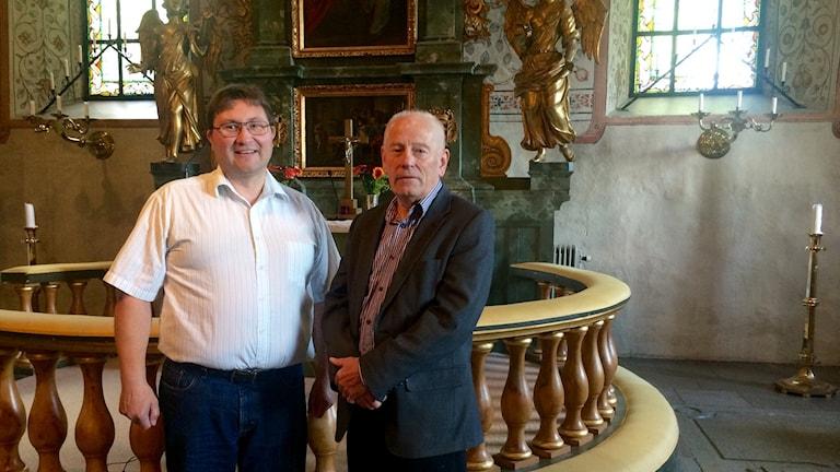 Två män står framför altare