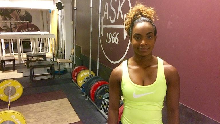 En kvinna står i en träningslokal.