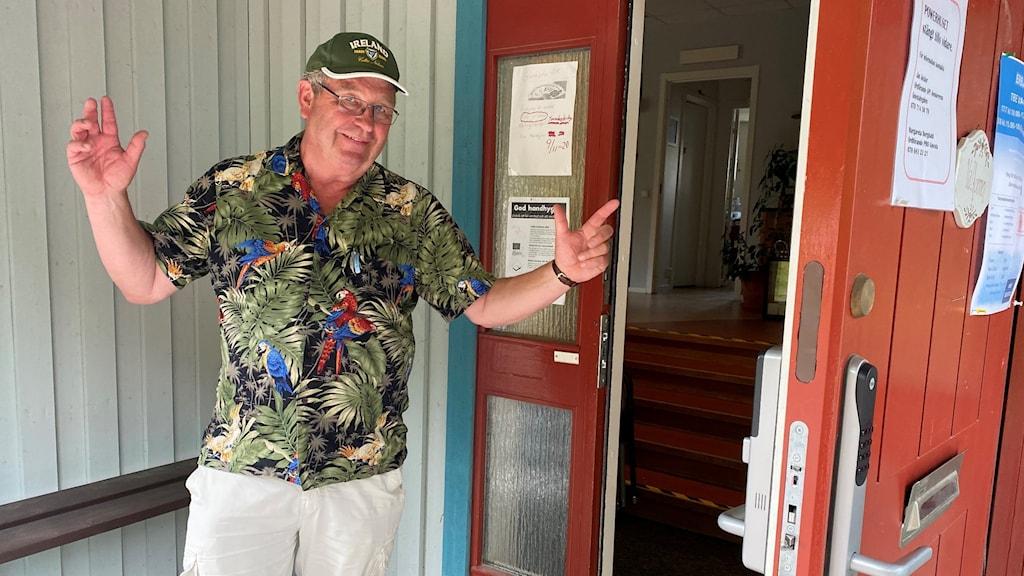 Man står med öppna armar framför en byggnad med öppen dörr.