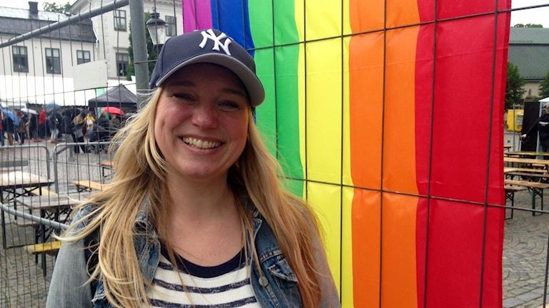 Camilla står framför regnbågsflagga