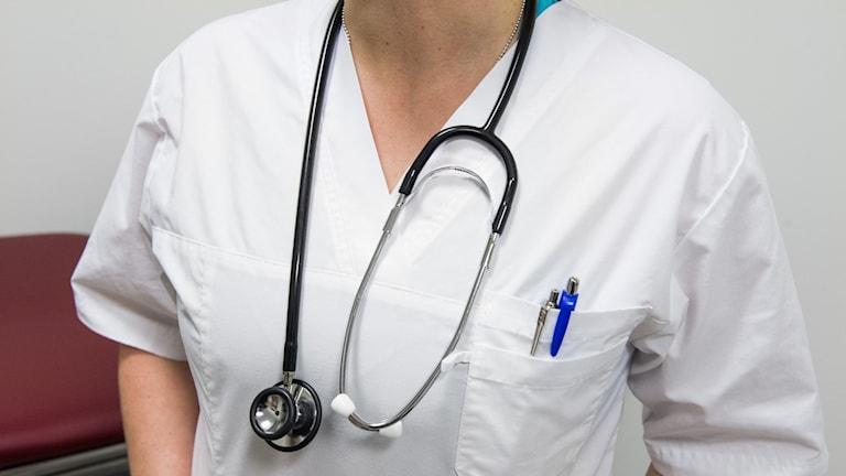Sjuksköterska på vårdcentral står med stetoskop runt halsen.