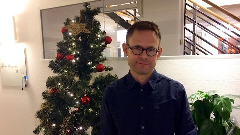 Jakob Håkansson, docent i psykologi vid Mälardalens högskola står framför en gran inomhus