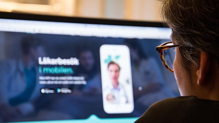 """Kvinna tittar på datorskärm. Står """"Läkarbesök i mobilen"""" på skärmen"""
