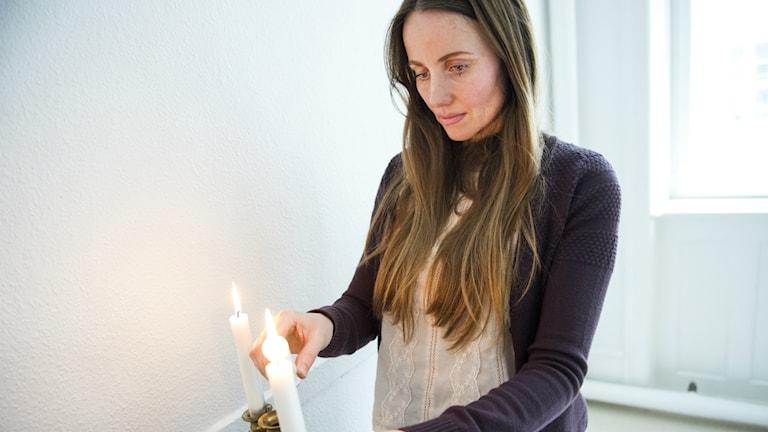 Kvinna tänder stearinljus