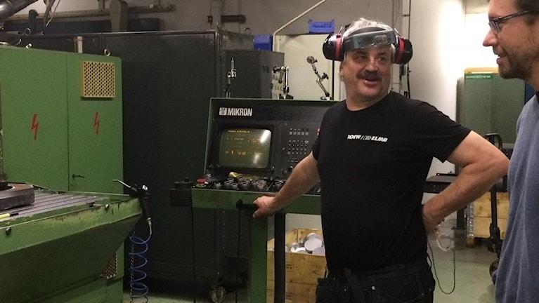 Mikael Lundblad, administrativ chef på Malmköpings mekaniska verkstad i Flen och arbetaren Henrik Andersson, som stått vid maskinen sedan 1986. Foto: Linnéa Wannefors/Sveriges Radio.