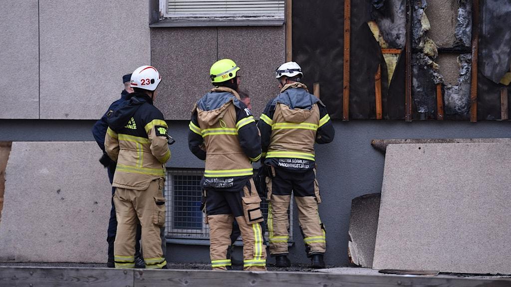 Brandmän tittar på en fasad som har brunnit. Foto: Pontus Stenberg.
