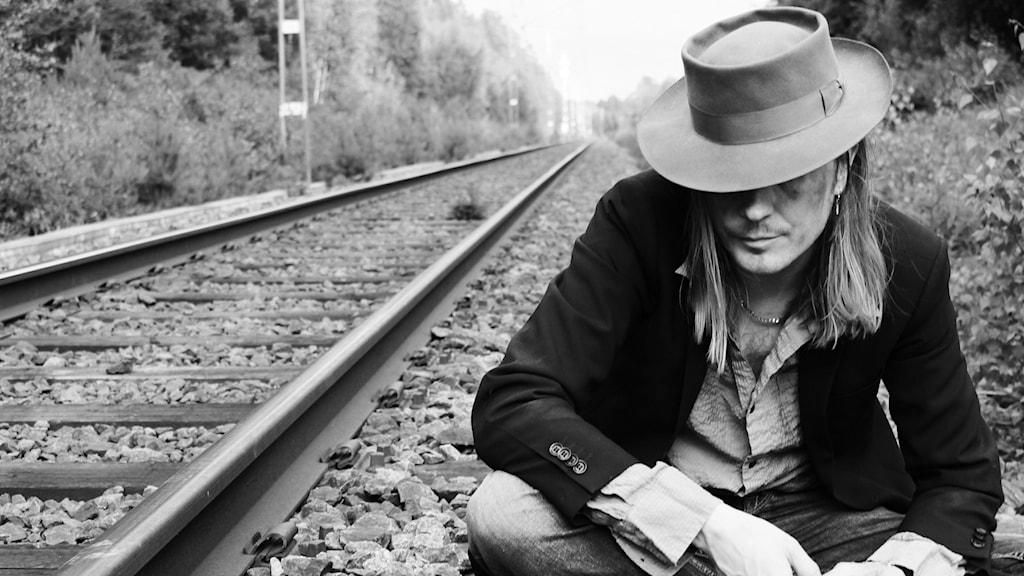 En man i hatt med brett bräde sitter hukad intill ett järnvägsspår. Bilden är svartvit.