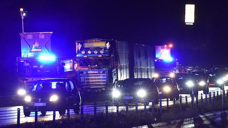 Bilar och lastbil på vägen. Skyltar om olycka.