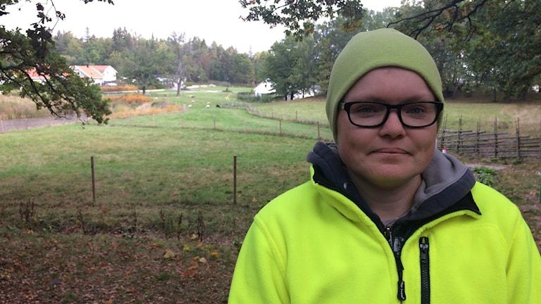 Marie Nilsson i en gul jacka, glasögon och grön mössa står framför en fårhage.