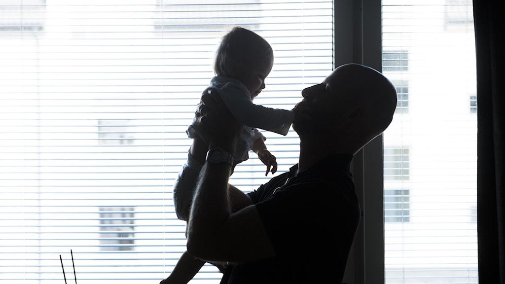 Pappa håller sitt lilla barn