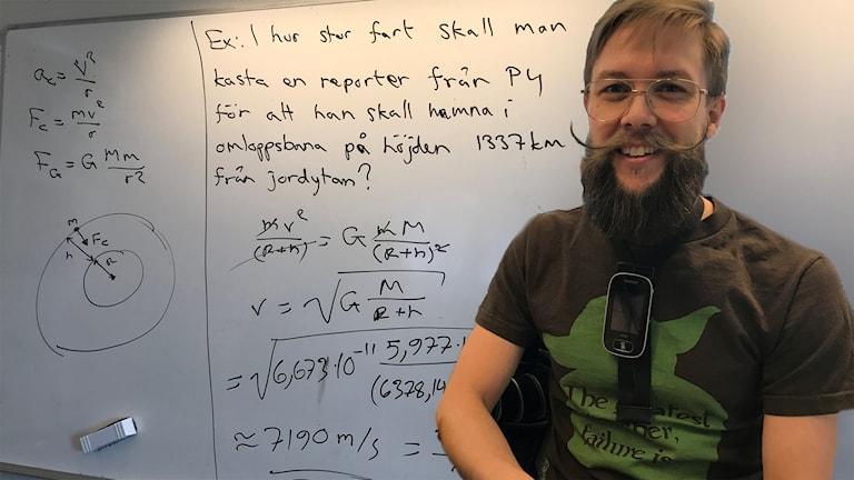 Whiteboard med fysiktal och Erik Waltersson, fysiklärare inklippt