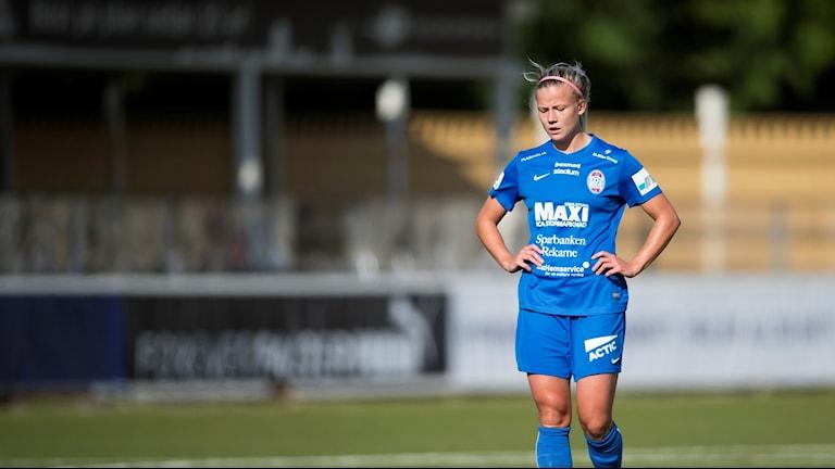En fotbollsspelare med blå dräkt står ensam på fotbollsplanen. hon har håret uppsatt.