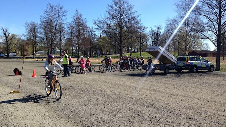 barn cyklar på grusplan