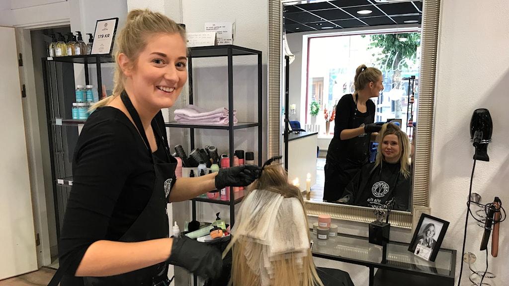Ida Plantin står bakom Josefhine Björn i frisörstolen.
