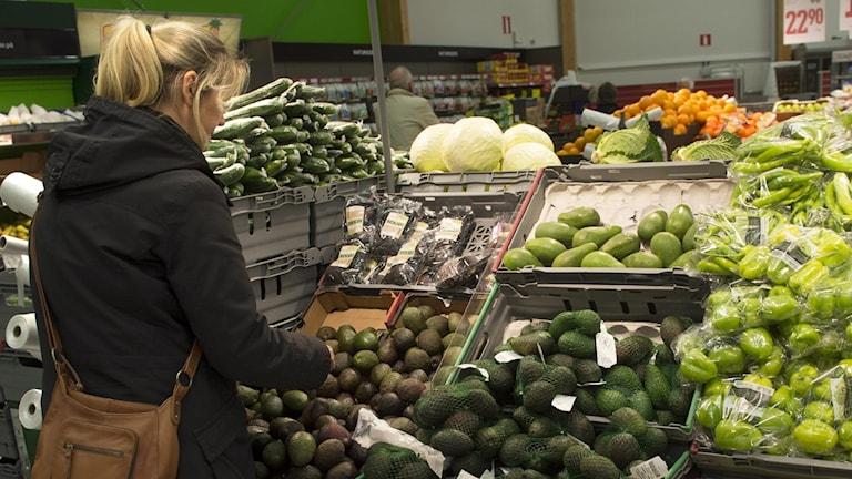 Person letar i frukt- och grönt-hyllan