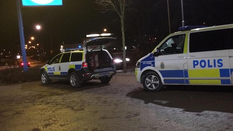 Två polisbilar i mörker. Foto: Fredrik Blomberg/Sveriges Radio.