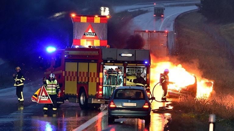 Bil brinner och räddningstjänsten släcker.