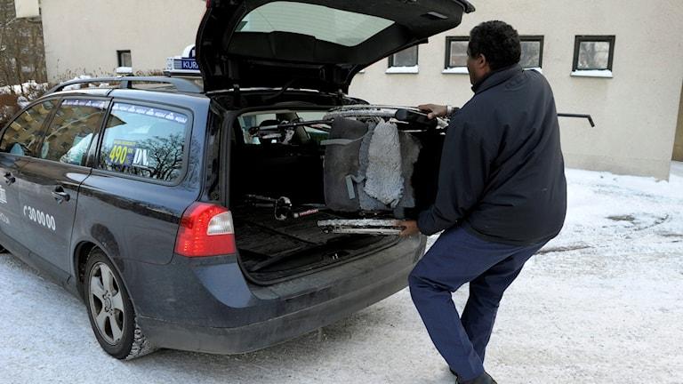 En färdtjänstchaufför lägger in en rullstol i bagageutrymmet på sin taxi Foto: Janerik Henriksson/TT.