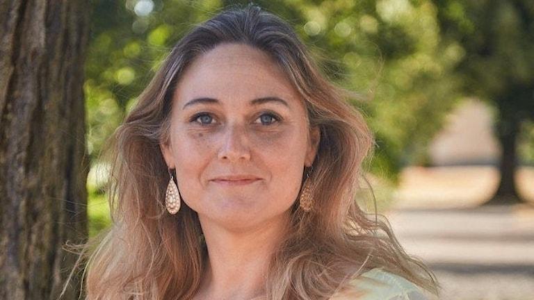 En kvinna med långt mellanblont hår och guldfärgade örhängen som står i en allé.