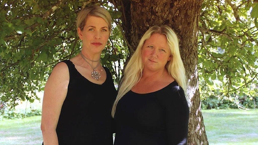 Två kvinnor står framför ett träd