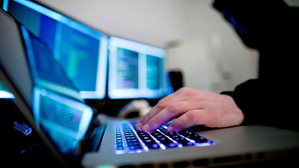Man med huva framför dator